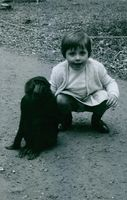 A cute little girl posing with a monkey and smiling.