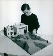 A boy playing the model house. November 1, 1953