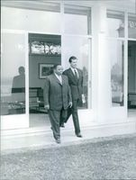 President of the Congo-Leopoldville (1960–65) Joseph Kasavubu walking with a man and coming out from house
