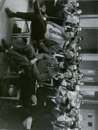 Group of men listening to a discussion.