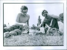 Men during picnic siting together, talking and cooking food.