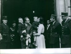 Man and woman standing with policemen and kissing their children.
