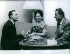 Renata Tebaldi listening two men conversation.