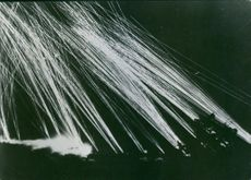 Anti-aircraft guns firing at Axis planes attacking Allied base in North Africa.