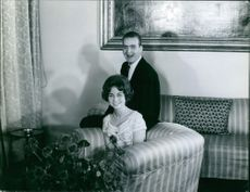 Juan Carlos and Queen Sofía of Spain sitting on couch and smiling. 1962.