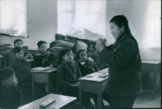 Teacher teaching in class to students.
