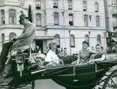 Karen Muir with two women, riding the open horse-drawn carriage.