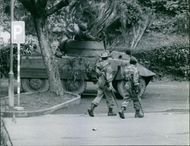 Soldiers walking in the camp, while another one moving through tank.1961