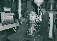 Apotekarnes Mineralvatten AB. Former Stig Cederberg, makes sure that the capsule is supplied with raw material, while a sewing man checks the bottled bottles