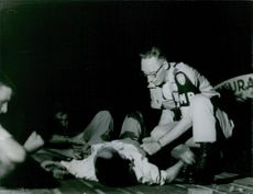 Medical aid worker tend on the wounded man lying on the floor. Saigon, 1965.