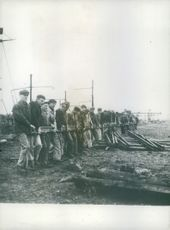 French workmen carry a track into place.