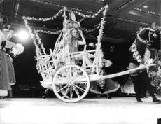 Woman sitting on horse cart, pulled by person on stage.