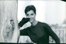 A woman in black dress and gloves strike a pose beside a tree.