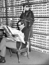 Roger Vadim sitting and reading the newspaper with Catherine Deneuve behind him.