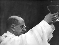 Pope Paul VI raising something.