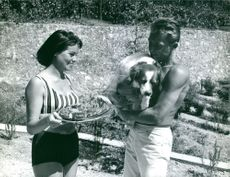 Georges Rivière holding his pet dog and communicating with his wife.
