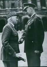 A military officer stood in front of a man in uniform while he smiles and holds his hand, 1959.