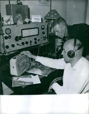Men sitting and operating the radio in the radio station.