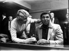 Muhammad Ali gets help with his make-up of the TV personality Tom O'Connor in anticipation of his involvement in a television feature about Joe Erskine.