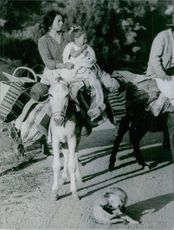 Vintage photo of a woman and child riding a donkey in Spain.