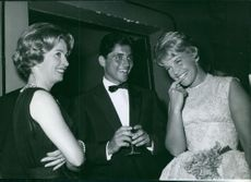 Sacha Distel having some fun with two female while talking.