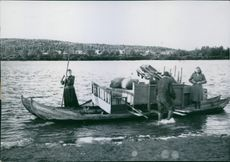 A boat loaded with baggage docked on the shore. 1944