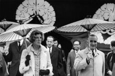 Georges Jean Raymond Pompidou  and wife Claude Jacqueline Pompidou both holding two different umbrellas made of straws.