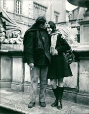 Janis Markopuoulos kissing a young woman on her forehead in Piazza S. Maria Trastevere, Rome.  Taken Jan. 1970