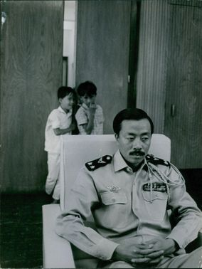 Nguyễn Cao Kỳ sitting on chair, behind him are his two children. 1966.