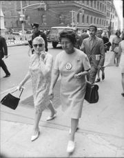 A woman walking on the street wearing a pin with the face of Robert F. Kennedy.