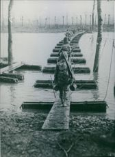 Soldiers in single file crossing a body of water though a foot path bridge.