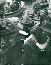 A man named Bob Maury and a woman hugging each other in a break water around people on boats watching them and smiling.
