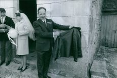 Man holding and showing coat, while a couple standing beside him. 1988