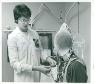 Professor David Ingvars assistant Elisabeth Svensson prepares patient for EEG measurement