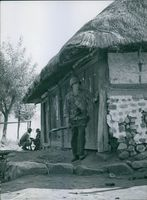 A soldier are looking something front of a house during The Korean War in 1950.