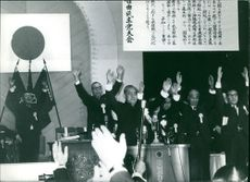 Eisaku Satō and other Japanese nationals raising their hands in a conference.  Taken - 20 Mar. 1989