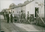 Photo of German men with their pet dogs.