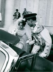 King Hussein assist Princess Muna Al Hussein in getting inside their vehicle after the wedding ceremony.