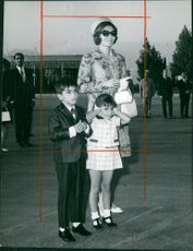 Farah Pahlavi standing together with her children Reza Pahlavi and Farahnaz Pahlavi.