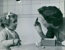 Woman and girl playing with animal toys.