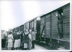 Soldiers from a train, waving to people in Austria while moving.