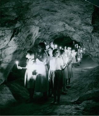 School girls visiting into a cave while holding a candle, 1951.