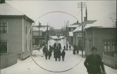 People seen through a circle walking along Stationsgatan in Lycksele.  1924 Posti of Stationsgatan Lycksele