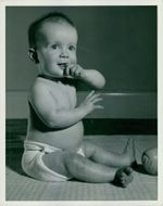 A toddler pictured sitting on a floor and biting his fingers.