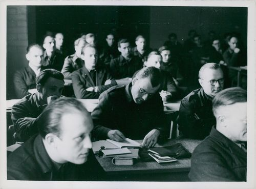 """One German bends his head to take notes at the camp to train the """"Future Rulers of Germany."""" Others in the class fold their arms as they listen. 1946"""
