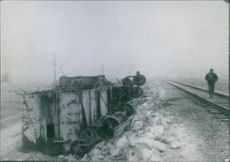 A soldier walking past the wreck beside the railway track.