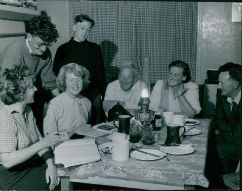 A photo of a happy  family in the dining table, reading books, talking and laughing together, with lighted lamp at the center of the table, October 1954.
