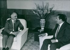 King Hussein talking to Hosni Mubarak while siting in the couch.