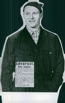 Man with woollen cap and sign from Trondheim police, warning  that red woollen caps are considered as demonstration and thus banned, Norway 1943.