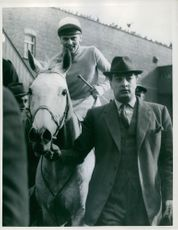 Nicolaus Silver with H. Beasley in the saddle is led in by the owner after winning the Grand National at Aintree, March 1961
